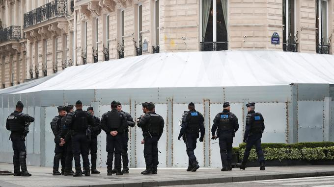 "French gendarmes and riot police officers secure the Champs-Elysees avenue in front of the famed restaurant Fouquet's during the Act XIX (the 19th consecutive national protest on a Saturday) of the ""yellow vests"" movement in Paris"